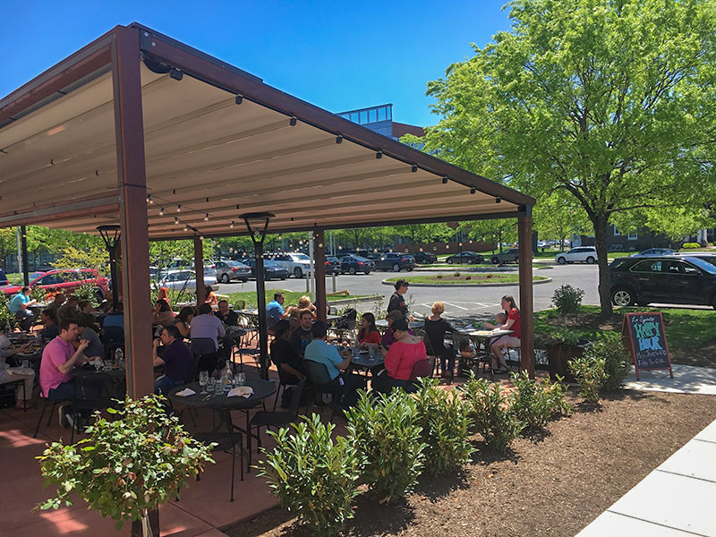 A Restaurant Patio With A Gennius Rectractable Awning